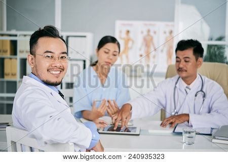 Cheerful Vietnamese Doctor Attending Conference Of Medical People