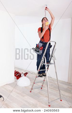 Handywoman fixate a lamp on the ceiling