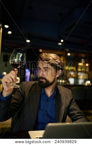 Sommelier Looking At Red Wine In Glass To Analyze Quality And Writing In His Blog