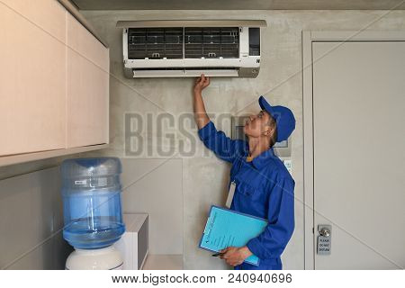 Young Asian Technician Checking Conditioner In Kitchen