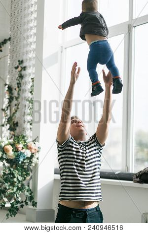 Happy Dad Throw Up His Son In Studio Interior. Window On Background.