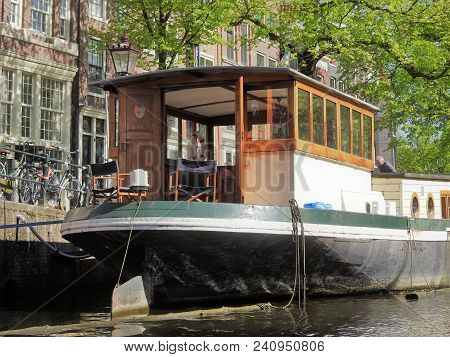 A Black And White Boat Parked At A Canal, On A Sunny Spring Day. Taken In Amsterdam.