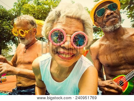 Cool seniors acting youtful by a swimming pool