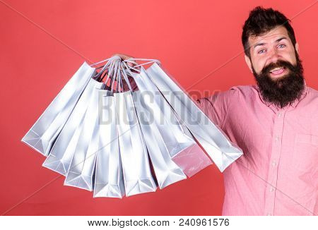 Man With Beard And Mustache Holds Shopping Bags, Red Background. Hipster On Happy Face Is Shopping A