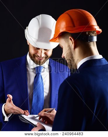 Colleagues In Helmets Discuss Building Plans. Engineers With Smiling Faces Look At Project. Business
