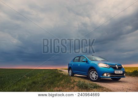 Gomel, Belarus - May 15, 2018: Reno Logan Blue Car Parked In The Field Against A Stormy Sky.
