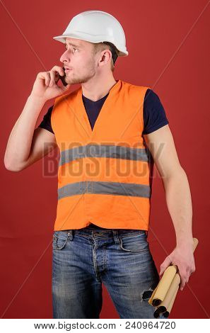 Man, Foreman In Helmet Speaking On Phone, Red Background. Architect Calling Engineer To Fix Plan. En