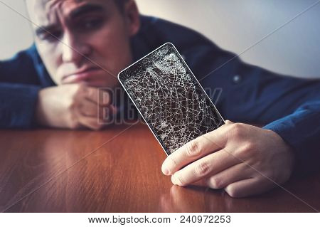 Hands Holding A Mobile Phone With A Broken Screen Over The Wooden Surface. A Man Looks At His Broken