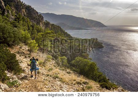 Man With Backpack Standing On A Cliff In Mountains Above Mediterranean Sea With Beautiful View Oppos