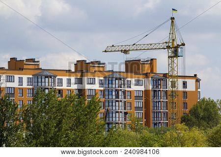 Urban View Of Silhouettes Of High Industrial Tower Crane Above Green Tree Tops Working At Constructi