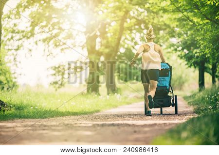Running Woman With Baby Stroller Enjoying Summer Day In Park. Jogging Or Power Walking Supermom, Act