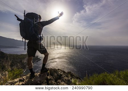 Man With Backpack And Hands Up Standing On A Cliff In Mountains Above Mediterranean Sea With Beautif