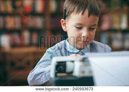 Serious Preschool Journalist Boy Sitting At Table And Typing Typewriter With A Pencil On The Top Of