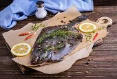 Raw flounder plaice fish (flatfish). Cooking process concept. Flounder fish with spices, lemon slices, thyme on parchment paper. Dark wooden table background. poster