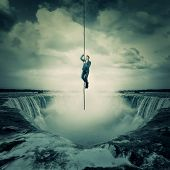 Businessman salvation, surviving the storm buiness concept as a scared man hanging on a chain escape above a waterfall, trying to climb up. Risk symbol, metaphor for conquering adversity and overcoming challenges. poster