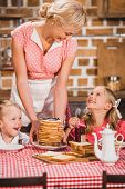 happy mother putting pancakes on table and looking at cute smiling kids having breakfast, 50s style family poster
