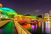 Clarke Quay bridge and Riverside area at evening in Singapore, Southeast Asia. Waterfront skyline reflected on Singapore River. Popular attraction for nightlife. poster