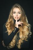 Luxury look. Cosmetic, beauty, skincare, haircare concept - passionate sexy blonde woman with healthy long hair, perfect makeup. Sensual blonde model with gorgeous hair in black clothes shows sign shh poster