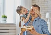 Happy father's day! Child daughter congratulating dad and giving him gift box. Daddy and girl smiling and hugging. Family holiday and togetherness. poster