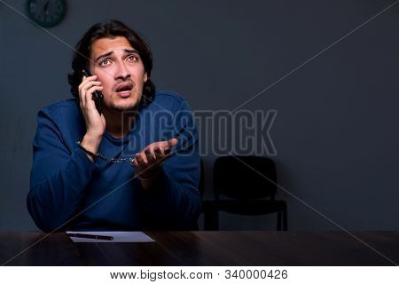 Young convict man sitting in dark room