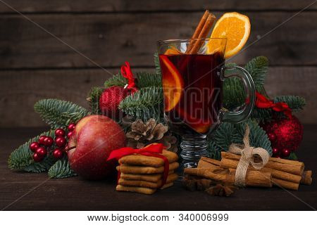 Mulled Wine With Cinnamon Sticks Orange Fir Tree Branch And Baubles Christmas Composition Over Dark