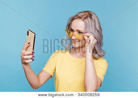 Blond Young Happy Woman In The Tellow T-shurt And Sunglasses In The Blue Studio.