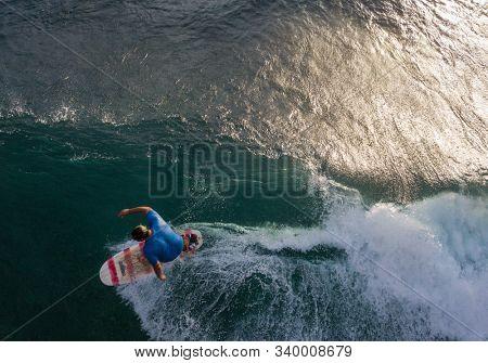 OAHU, HI / USA - NOVEMBER 15,2018: Surfer rides the ocean wave