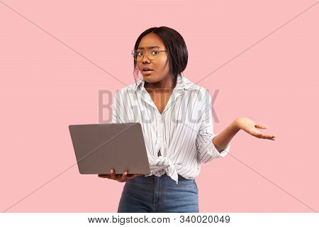 Discontented Afro Girl Holding Laptop And Shrugging Shoulders Having Problem Standing Over Pink Back