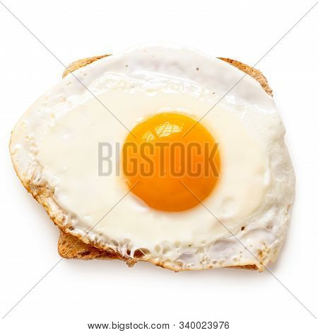 Single Fried Egg With Crispy Edges On Wholewheat Toast Isolated On White. Top View.
