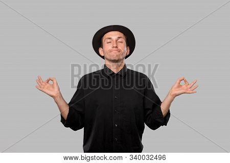 Stylish Handsome Man A Black Shirt And Pork Pie Hat Smiling Meditating Over Grey Background. Concept