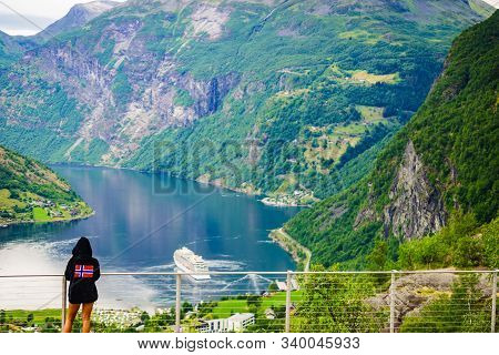 Tourist Wearing Norwegian Flag Clothing Enjoying Scenic View Over Fjord Geirangerfjorden From Flydal