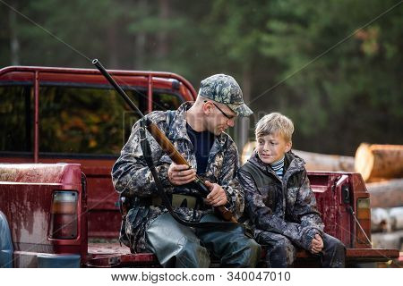 Man At His Truck With His Son In The Forest. Hunter Teaches Young Boy How To Use Shotgun Rifle.