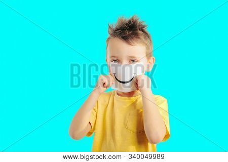 Little child holding a card with smiling face. Boy chooses an emotional faces. Photo on a color background