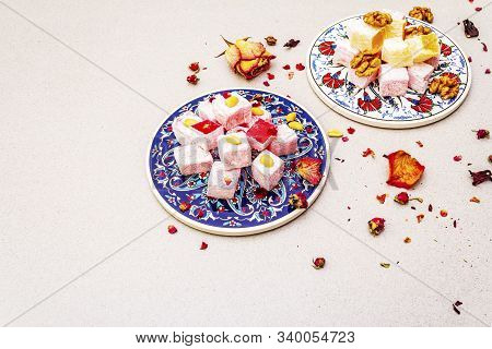 Eastern sweets. Traditional Turkish delight Rahat lukum with a rose and citrus on ceramics with typical folk patterns. Stone background, copy space, top view poster