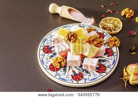 Eastern sweets. Traditional Turkish delight Rahat lukum with rose and citrus on ceramics with typical folk patterns. Raspberry and strawberry sugar, sumac in wooden shovels, stone background top view poster