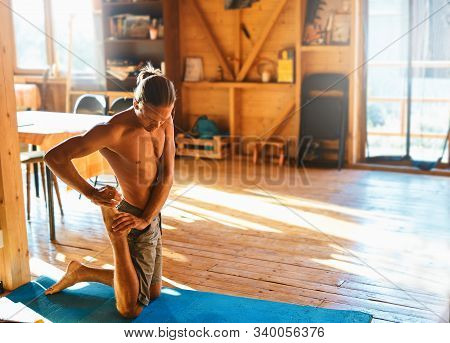 Strong Athletic Handsome Tanned Man With Naked Torso Doing Stretching At Home In Wooden Room At Sunn