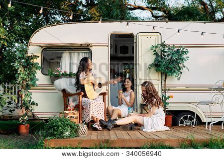 Laughing Happy Women With Guitar Have Fun Together Outdoors Near Their Camper Van During Summer Trav