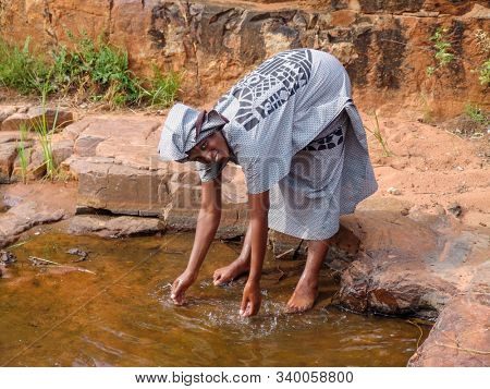 african woman in a village in Botswana washing her hands in a puddle, water scarcity, draught