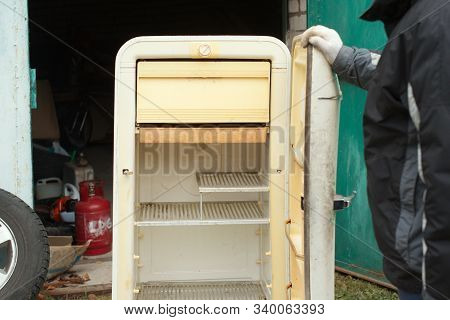 A Man About To Discard Old Fridge Standing Next To The Open Garage Door, Outdoor Cropped Shot