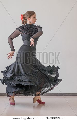 Beautiful Young Woman In A Black Elegant Dress And A Red Flower In Her Hair Is Dancing Flamenco On A