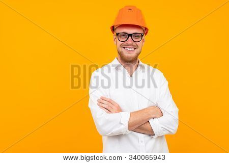 Beautiful Caucasian Engineer Man With Glasses And Orange Helmet Isolated On Yellow Background.