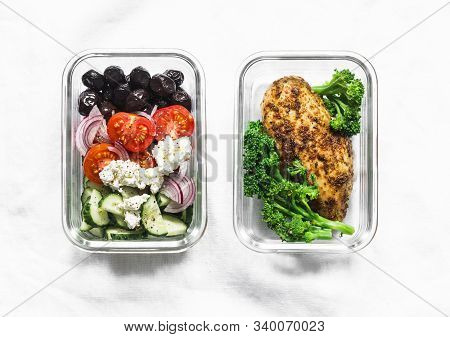Two Healthy Balanced Lunch Boxes With Greek Salad, Baked Chicken Breast And Broccoli On A Light Back