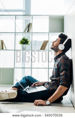 Side View Of Handsome And Smiling Bi-racial Man With Laptop Listening Music