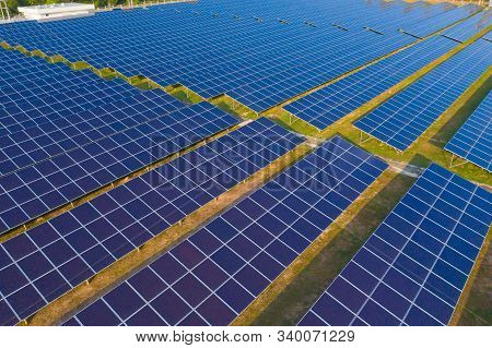 Aerial View Of Solar Panels Or Solar Cells On The Roof In Farm. Power Plant With Green Field, Renewa