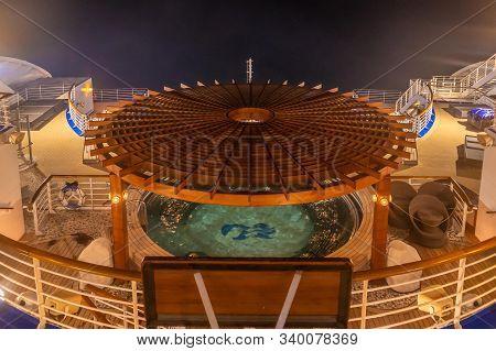 Back Balcony Of Diamond Princess Cruise Ship With Service Bar And Swimming Pool At Night.