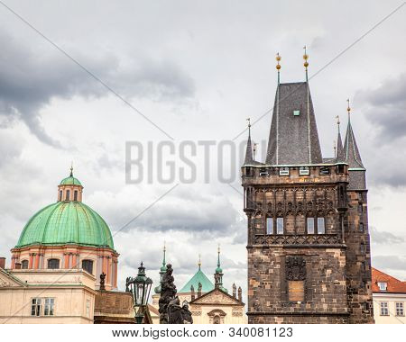 Urban scene with old Town Bridge Tower and St. Francis Of Assisi Church in Prague, Czech Republic in cloudy summer day.
