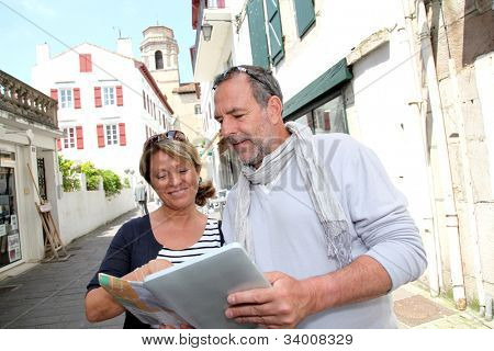 Mature couple in seaside resort looking at map
