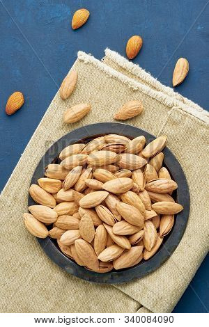 Top View Plate With Almonds In Endocarp, Bowl With Drupe In Shell On A Linen Napkin On Dark Blue Bac