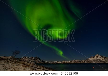 Aurora Borealis, Polar Lights. Northern Lights With Many Stars On The Sky Over Mountains In The Nort