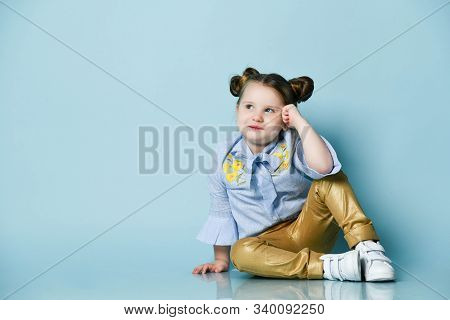 Smiling Frolic Little Baby Kid Girl In Blue Shirt And Gold Leather Pants Is Sitting On The Floor Loo